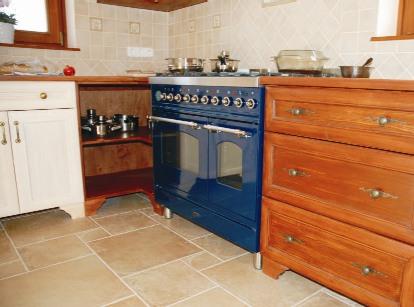 A tűzhely kék színét jól ellensúlyozza a környezetében levő bútor meleg fa színe