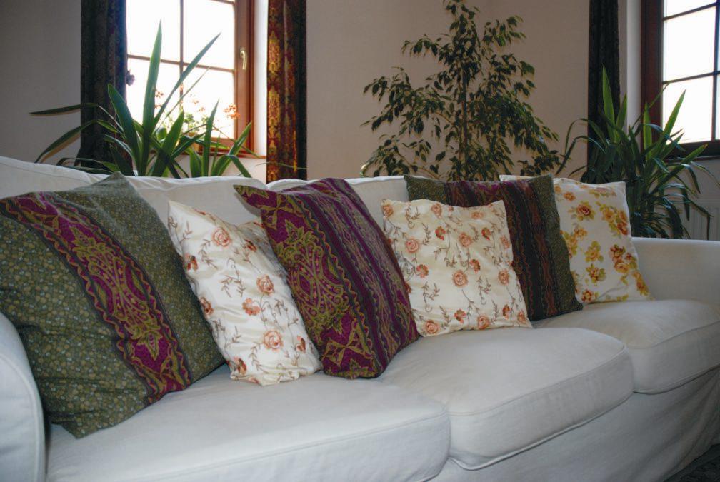 Ugyanaz a kanapé nyáriasabb párnákkal. A sötétebb párnák azért maradtak a kapanpén, mert egyrészt a szoba délnyugaton van, másrészt a sötét párnák a függöny anyagával harmonizálnak.