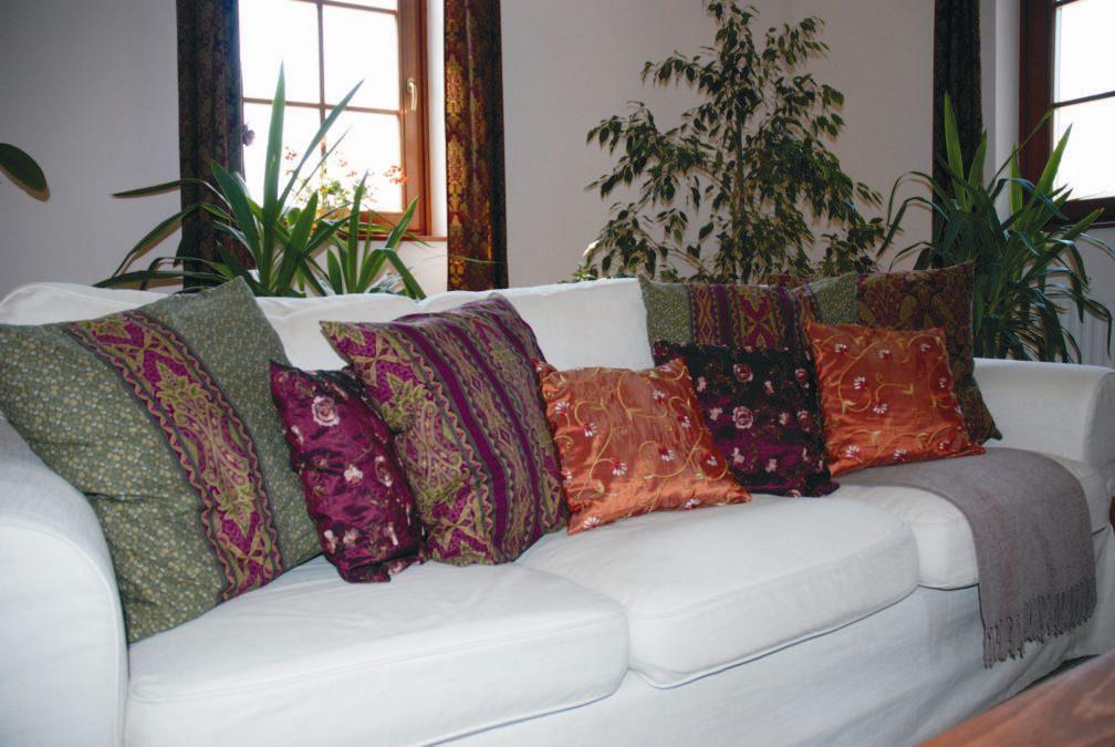 """Világos színű kanapé meleg színű díszpárnákkal és pléddel """"téliesítve"""""""