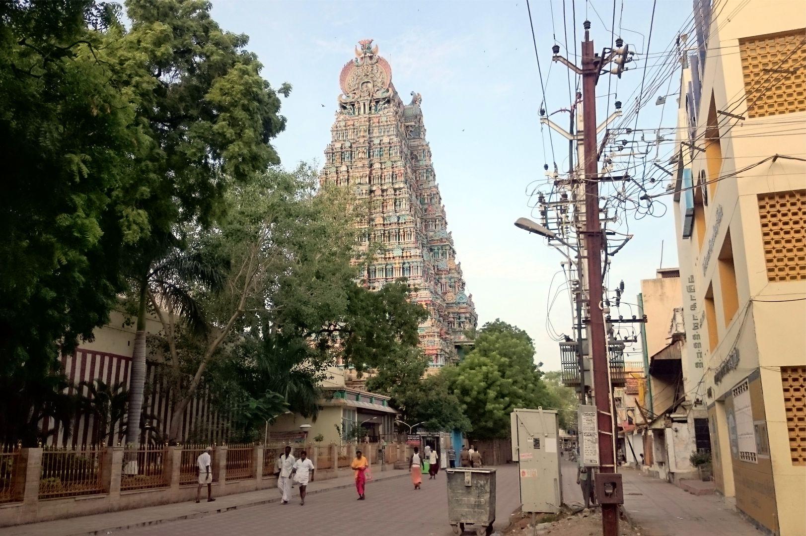 A híres Menaksi templom egyik gopuramja Maduraiban. A fotó baloldalán látható vörös-fehér csíkor fal a templom komplexum külső fala, a kép jobb oldalán pedig megcsodálhatod az indiai villanyszerelés egy konszolidált példáját...