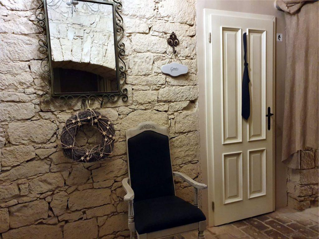 Egy építész vagy lakberendező alkotása látványos, kreatív ötleteivel kényelmes és szép épületeket, belső tereket hoz létre. (A kép egy étterem alagsorában, a mellékhelyiségekhez vezető folyosón kíészült. Az ajtóra akasztott nyakkendő jelzni, hogy abba a helyiségbe az urakat várják.)